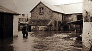 Curly Knight in flooded river at Score Farm 1960-61.  Floods have occurred throughout the village's history.  At one time, people who arrived at Braunton Station from Barnstaple or Ilfracombe were cut off from the east side of the village. To overcome this difficulty some sailors and fishermen hurried to Vellator and brought a boat to the flooded street. They did a good trade ferrying marooned travellers backwards and forwards.  Courtesy of Braunton Museum.
