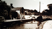 This picture-postcard shows the bridge that crosses the River Caen next to Score Farm in 1931.  On the opposite side of the bridge, Horden's Mill was once located. This Mill would have used the River Caen to turn the mill wheel, which ground barley to be used as feed for the villagers
