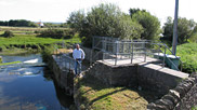 Caption – Richard Dyer, shown here at the weir, is the Chairman of the Braunton Marshes Internal Drainage Board.  To his right can be seen part of a modern set-up, which was installed to control the water level on the marshes.  It was, however, not as effective as the traditional method, which has since been reinstated.  Part of the original workings can be seen at Richard's feet.  Courtesy of Dave Edgcombe.